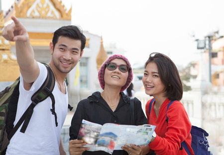 advice: traveling man woman and senior tourist holding travel guide book in hand pointing to destination for visiting