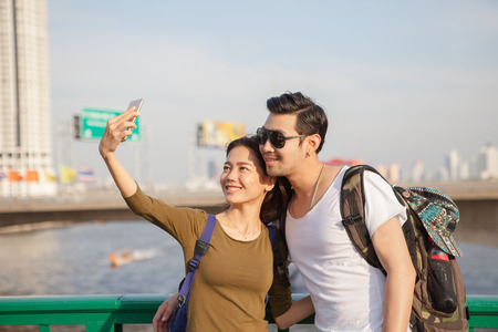 younger man: couples of younger man and woman take a selfie photograph by smart phone on traveling location
