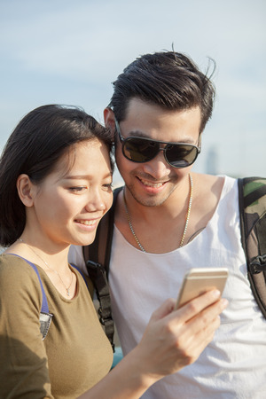 communicated: close up face of younger asian man and woman looking to smart phone use for young people digital techmology lifestyle Stock Photo