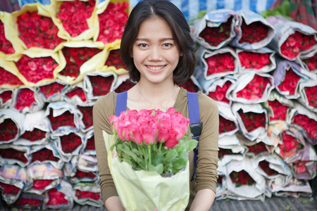 younger: smiling face of younger asian woman with pink roses flower bouquet in hand Stock Photo