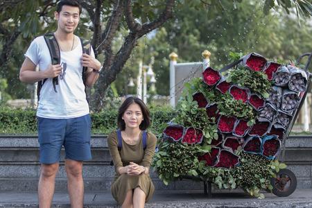 bouquet fleur: couples portrait de jeune homme voyage asiatique et femme assis à côté de la route à côté de roses rouges bouquet de fleurs