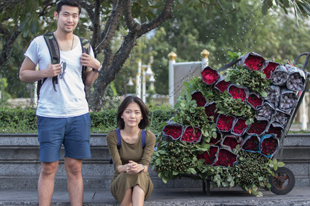 younger: portrait couples of younger asian traveling man and woman sitting at road side beside red roses flower bouquet