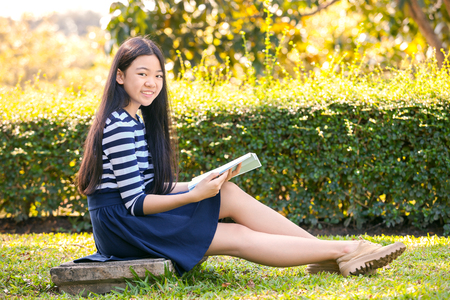 grade school age: portrait of asian teen twelve years old and school book in hand with toothy smiling face Stock Photo