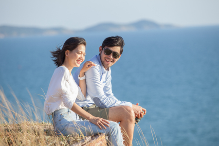young asian couple: portrait of asian younger man and woman relaxing vacation at sea side happiness emotion Stock Photo
