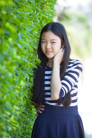 caras felices: retrato de joven adolescente asiática con emoción felicidad y la cara sonriente en el parque verde