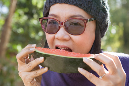 water melon: close up face of young woman earting water melon