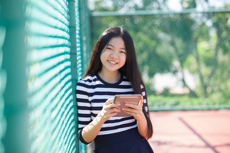 technolgy: asian girl and computer tablet in hand standing with toothy smiling face use for people and internet connecting ,communication in modern digital lifestyle Stock Photo
