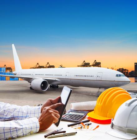 toucher de la main sur la tablette d'ordinateur sur la table de travail contre le parking de l'avion d'air à l'aéroport de l'utilisation des pistes pour le fret, le fret logistique et le thème du transport aérien