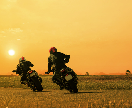 Couple of friends motorcycle rider biking on asphalt highway against beautiful sun set sky.
