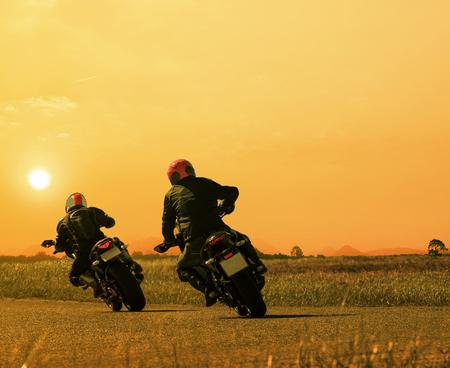 out of doors: Couple of friends motorcycle rider biking on asphalt highway against beautiful sun set sky.