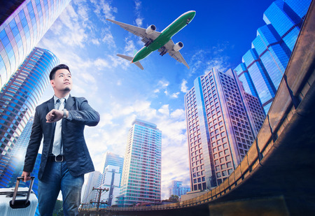 citylife: young business man standing against urban building scene looking to sky with passenger jet plane flying above use for people in traveling theme
