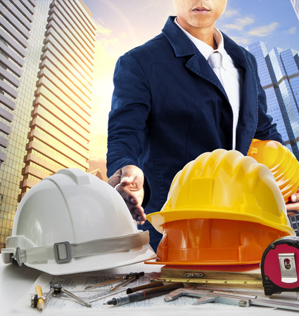 land use: engineer man and working table against sky scrapper in urban scene use for land development and architecture occupation theme Stock Photo