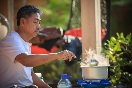 old gas stove: old man cooking morning food meal in hot pot on lpg gas stove Stock Photo