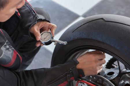 man checking motorcycle tire pressure Foto de archivo