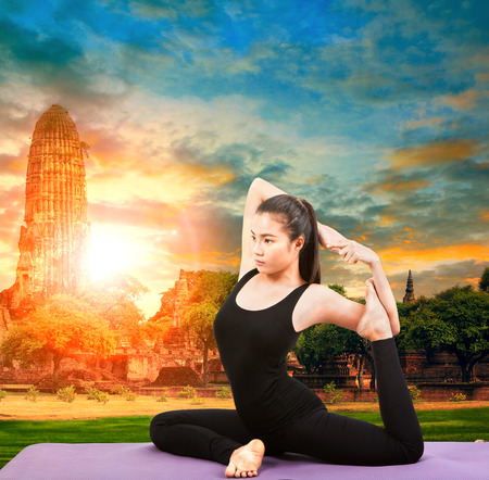 posting: asian woman health care yoga posting with asian ancient pagoda temple and sun set sky