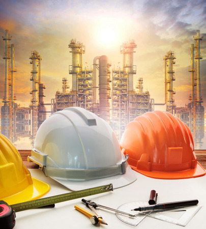industria petroquimica: engineer working table plan, and oil refinery plant in heavy petrochemical industry