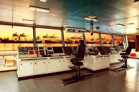 wheelhouse control board of modern industry ship approaching to harbor at night Editorial