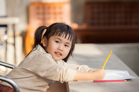doing: asian children with yellow pencil in hand doing school home work with happiness emotion