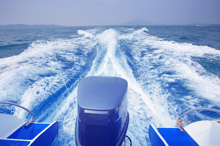 out of doors: rear view of speed boat running high speed on blue sea water use for traveling to island destination Stock Photo