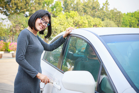 open car door: asian woman with smiling face open passenger car with a vehicle smart key