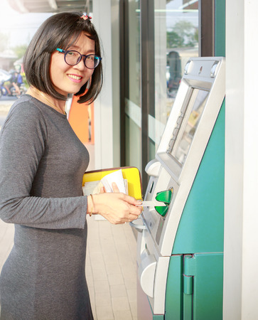 asian lady: asian woman smiling face happiness emotion standing in front of automatic teller machine withdraw cash from internet banking