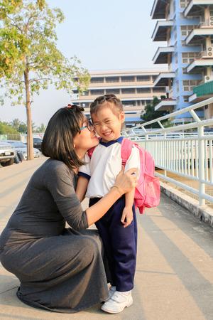 go to school: la madre y el niño adorable con mochila escolar frente a la escuela pre jardín de infancia