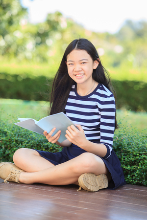 library book: asian girl and school book in hand toothy smiling face with happiness emotion in green park
