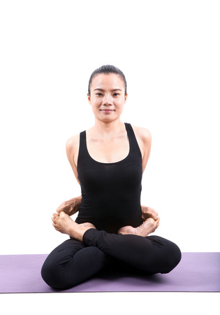 meditation room: portrait of asian woman wearing black body suit sitting in yoga meditation position isolated white background