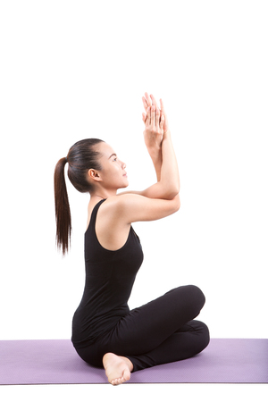 basic care: portrait of asian woman wearing black body suit sitting in yoga meditation position isolated white background