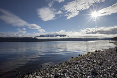 skie: sun light over lake te anau fiordland national park new zealand