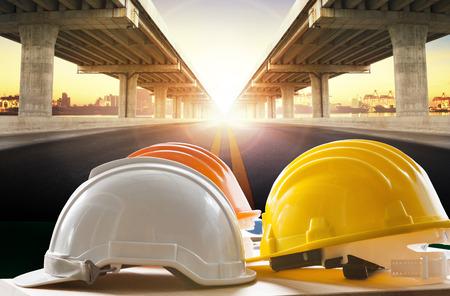 casco de seguridad en la mesa de trabajo de ingeniería civil en contra de la construcción de puentes en la escena urbana Foto de archivo