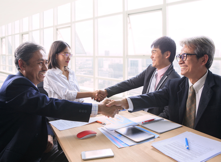 happy customer: team of man and woman  business people successful shaking hand after solution meeting agreement shot in office room