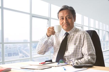 年配の作業男性顔の幸せの感情を笑顔のオフィスの部屋で飲み物を飲むとリラックス