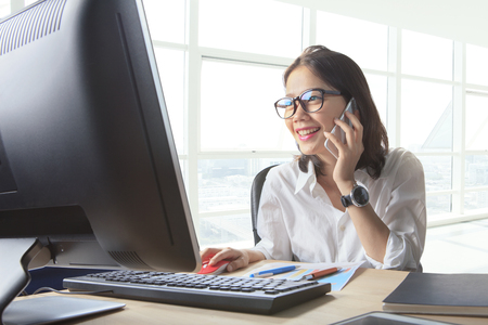 young working woman talking to phone with watching on computer on office table use for business connecting ,customer service ,communication