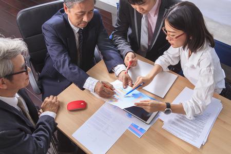 equipo de trabajo de negocios gente asiática informe de la reunión de análisis de discutir disparo de cepillado proyecto sobre la mesa de trabajo de oficina
