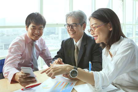 business activity: group of business people meeting with happiness emtion pointing to smart phone in hand use for modern working people lifestyle on digital technology