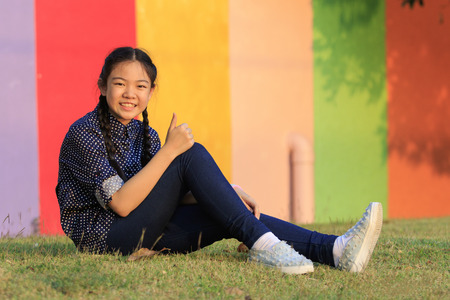 all right: asian girl relaxing sitting on green grass field of public park and hand sign ok ,all right with toothy smiling face happiness emotion