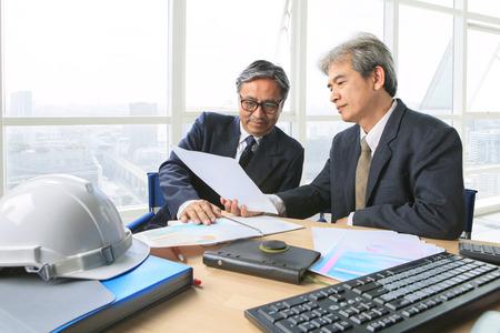 administrador de empresas: un socio de ingeniería de alto nivel de trabajo hombre serio reunión sobre el proyecto dicussing disparo solución sobre la mesa en la oficina sala de reuniones Foto de archivo