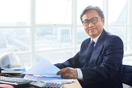 asia people: senior business man working on office table with smiling face happiness emotion