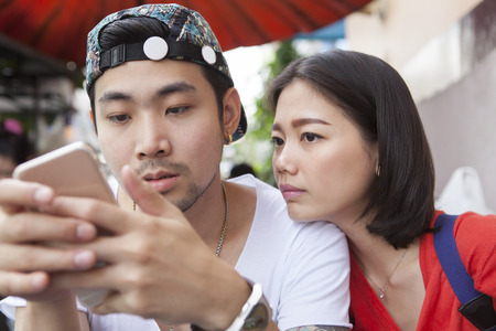 communicated: asian younger man and woman watching on smart phone use for people and digital technology ,wifi and internet connection