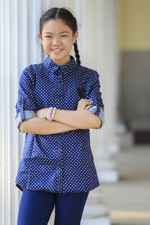 asia children: portrait of thai 12s years girl wearing blue shirt standing out door with toothy smiling face happiness emotion Stock Photo