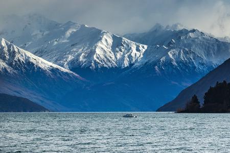 newzealand: snow mountain scene and motor boat over lake wanaka beautiful destination in south island new zealand