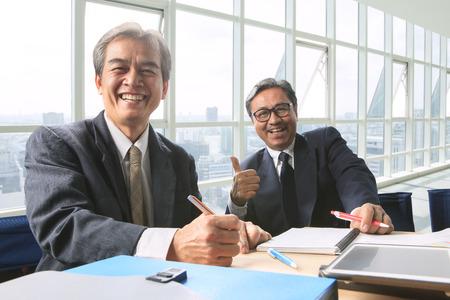 良いカップルの健康的な悪漢シニア作業撃たオフィス作業テーブルの幸福感情の笑い顔