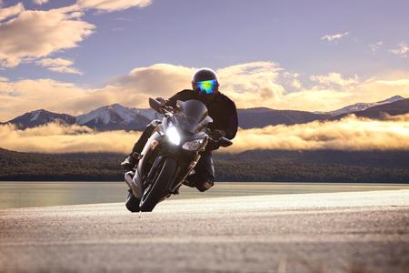 Jonge man rijden op grote fiets motorfiets tegen scherpe bocht van asfalt hoge manieren weg met landelijke meer scène gebruik voor mannelijke avontuurlijke activiteiten en motorsport hobby op vakantie vakantie Stockfoto - 53622232