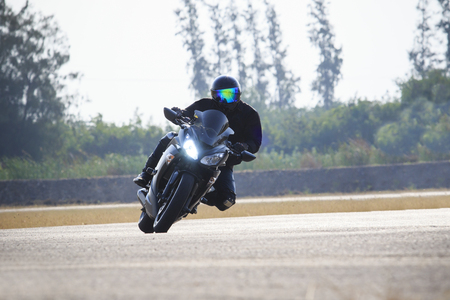 adventure holiday: young man riding big bike motorcycle against sharp curve of asphalt high ways road with rural lake scene use for male adventure activities and motor sport hobby on holiday vacation Stock Photo
