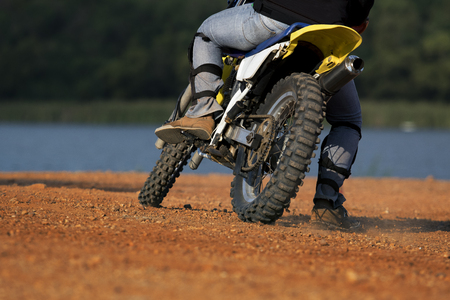 off road biking: man riding enduro motorcycle on dirt field