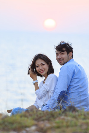 younger man: portrait of asian younger man and woman relaxing vacation at sea side happiness emotion against sun set sky background Stock Photo