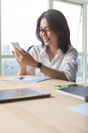 persona feliz: mujer que trabaja la lectura de mensajes en el teléfono inteligente con emoción felicidad disparo en la mesa de trabajo de oficina