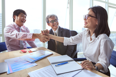 teamworking: business team work shaking hand in office meeting room with happiness emotion after discussing about project solution successful Stock Photo