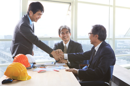 business asia: business man shaking hand after successful project solution planing meeting shot in office meeting room Stock Photo